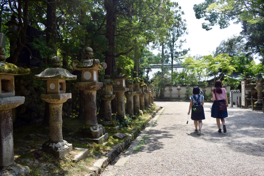 Two girls walk along the path that leads to the Kasuga-Taisha shrine. | Photo by Alexandra Pamias